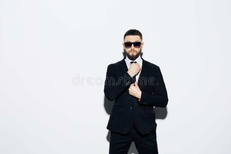 Hombre joven elegante en traje y gafas de sol Estilo del asunto Imagen de moda En fondo verde Hombre atractivo que coloca y que m fotografía de archivo