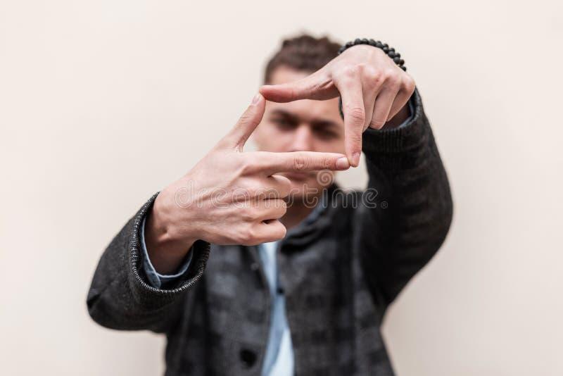 Hombre joven elegante fresco en la ropa de moda que muestra las manos a la cámara Presentaci?n atractiva del individuo Foco en la foto de archivo libre de regalías