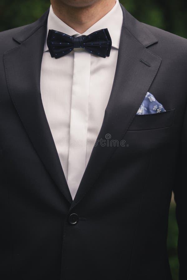 Hombre joven elegante hermoso de la moda en traje y corbata de lazo clásicos del traje del smoking de la capa Hombre de negocios  fotos de archivo