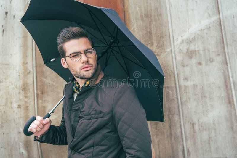 hombre joven elegante hermoso en las lentes que celebran el paraguas y la mirada fotos de archivo