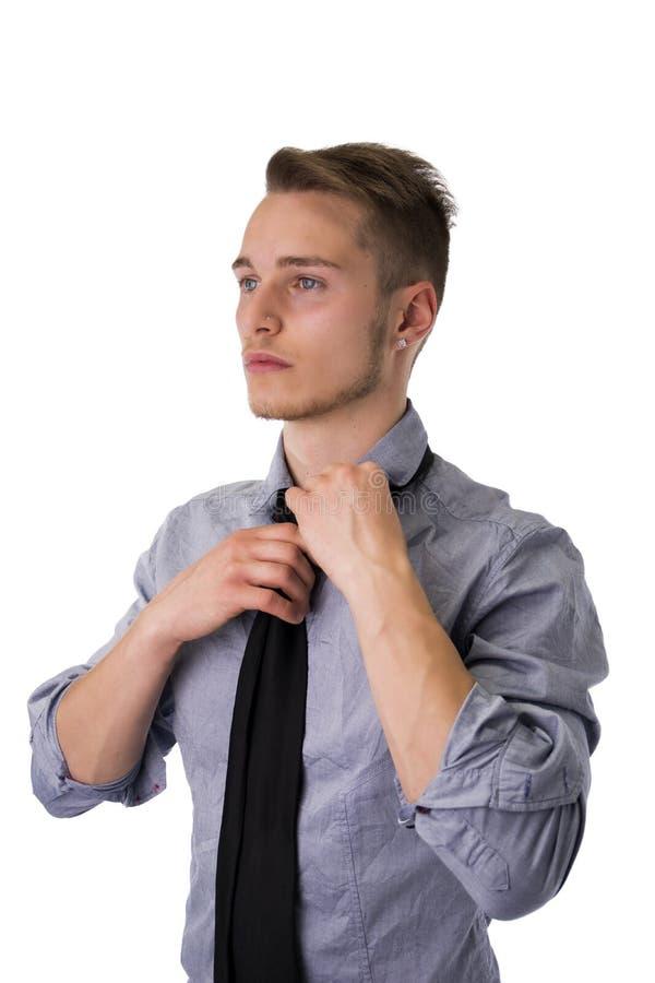 Hombre joven elegante que lleva y que ajusta la corbata fotografía de archivo