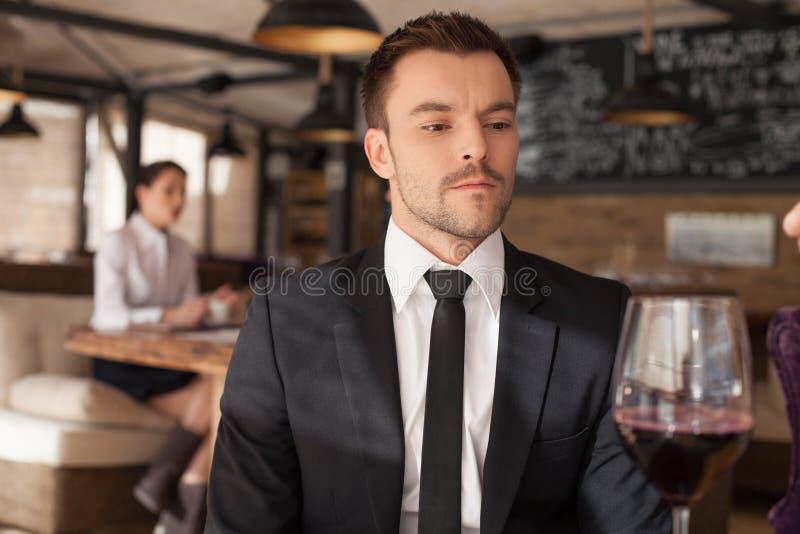 Hombre joven elegante que se sienta en barra imagenes de archivo