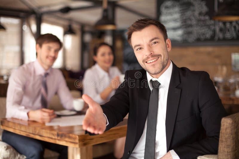 Hombre joven elegante que se sienta en restaurante imagen de archivo