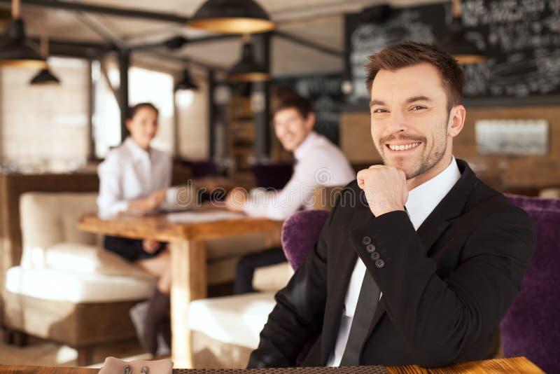 Hombre joven elegante que se sienta en restaurante fotos de archivo libres de regalías