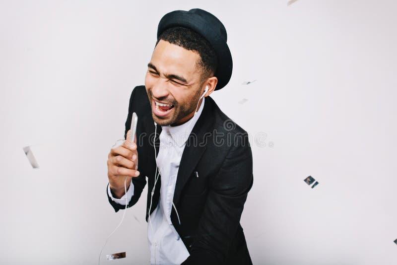 Hombre joven emocionado divertido en el traje que se divierte, riendo en el fondo blanco Ocio, sonriendo, cantando, escuchando la imagenes de archivo