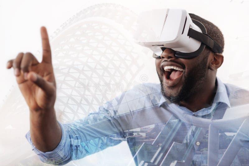 Hombre joven emocionado que lleva el dispositivo virtual imagen de archivo