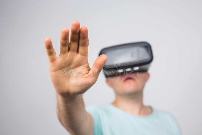 Hombre joven emocionado que usa auriculares de VR y experimentando la realidad virtual aislada en fondo gris fotografía de archivo libre de regalías