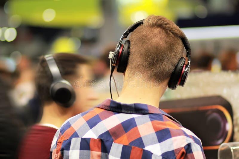 Hombre joven en auriculares comprobados de moda de la prueba de la camisa en tienda de la tecnología de la música Haciendo compra imagen de archivo libre de regalías