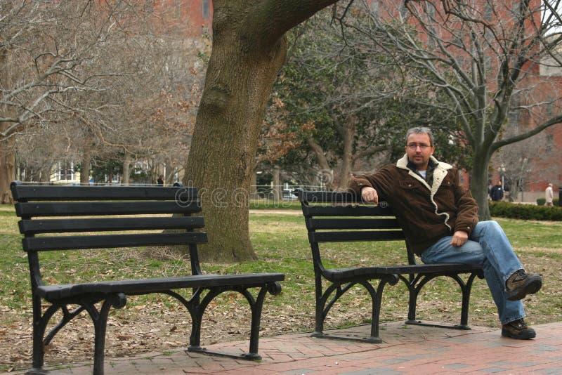 Hombre joven en banco de parque fotografía de archivo