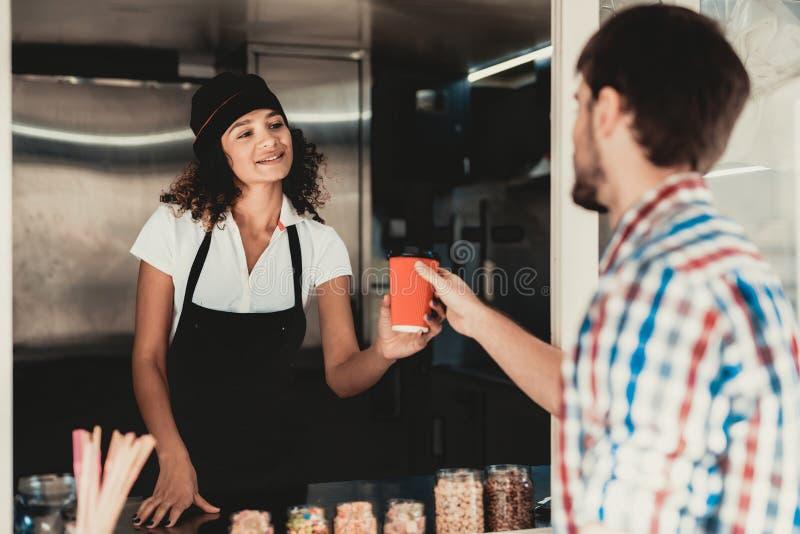 Hombre joven en café de la compra de la camisa en el camión de la comida 'promenade' en ciudad Árbol en campo Individuo en camisa imagen de archivo