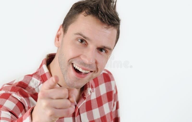 Hombre joven en camisa del inconformista que señala su finger en la cámara y la situación contra el fondo blanco foto de archivo