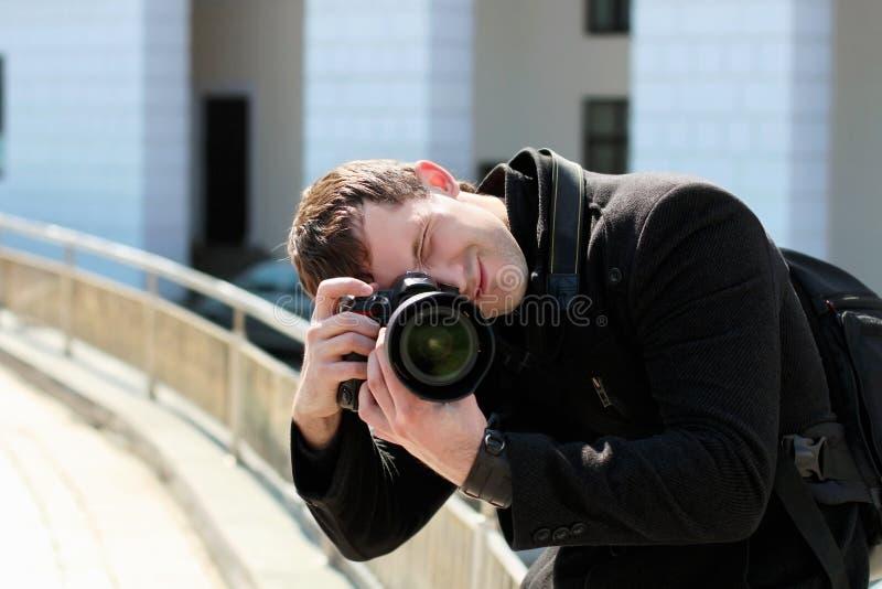 Hombre joven en capa negra imagen de archivo libre de regalías