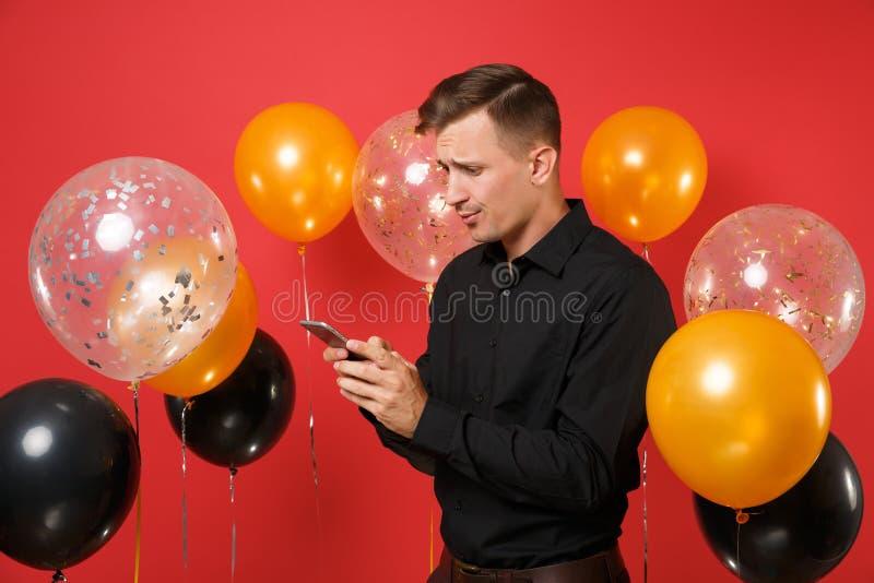 Hombre joven en cuestión en la tenencia clásica negra de la camisa, usando el teléfono móvil, mensaje del SMS que mecanografía en imagen de archivo