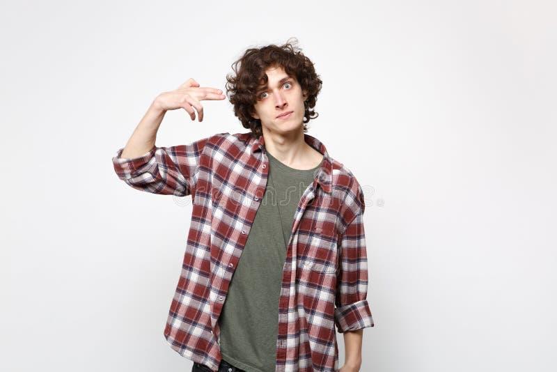 Hombre joven en cuestión Shocked en fingeres del punto de la ropa casual a la cabeza como si él se tire alrededor aislado en blan fotografía de archivo