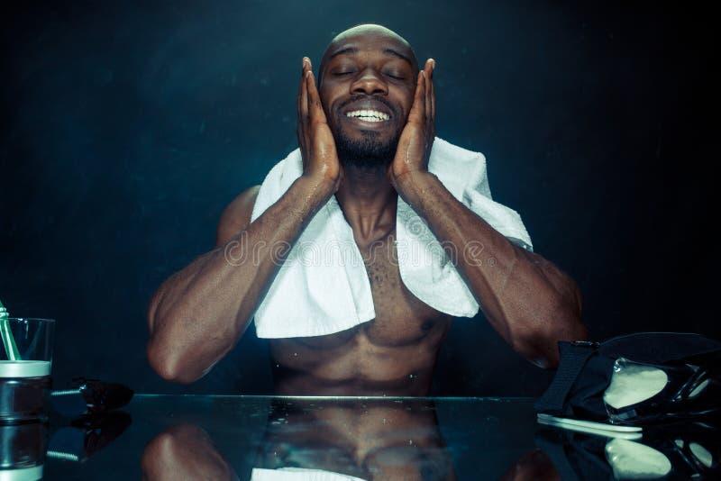 Hombre joven en el dormitorio que se sienta delante del espejo después de rasguñar su barba imágenes de archivo libres de regalías