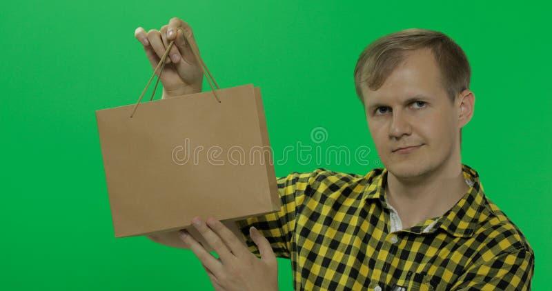 Hombre joven en el fondo dominante de la croma verde de la pantalla con el bolso de compras imagen de archivo libre de regalías