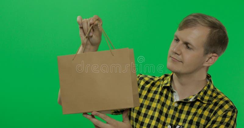 Hombre joven en el fondo dominante de la croma verde de la pantalla con el bolso de compras foto de archivo