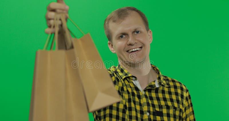 Hombre joven en el fondo dominante de la croma verde de la pantalla con los bolsos de compras foto de archivo libre de regalías