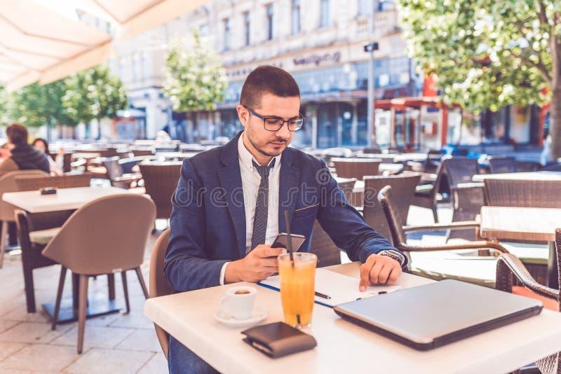Hombre joven en el funcionamiento de vidrios con smartphone y documentos en el café al aire libre fotos de archivo
