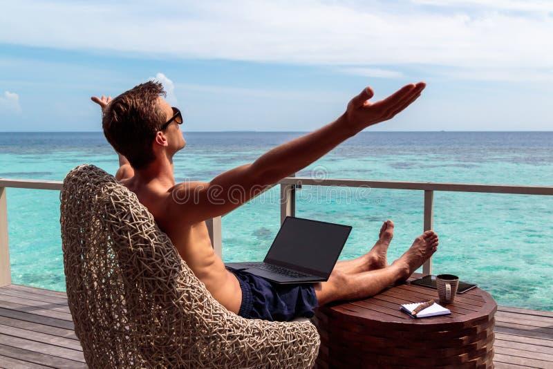 Hombre joven en el funcionamiento del traje de ba?o en un ordenador port?til en un destino tropical los brazos aumentaron, concep foto de archivo libre de regalías