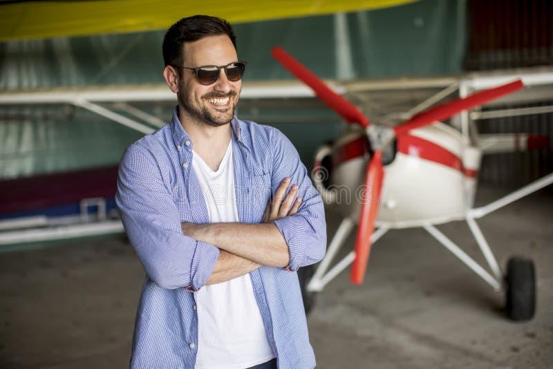 Hombre joven en el hangar del aeroplano imagen de archivo