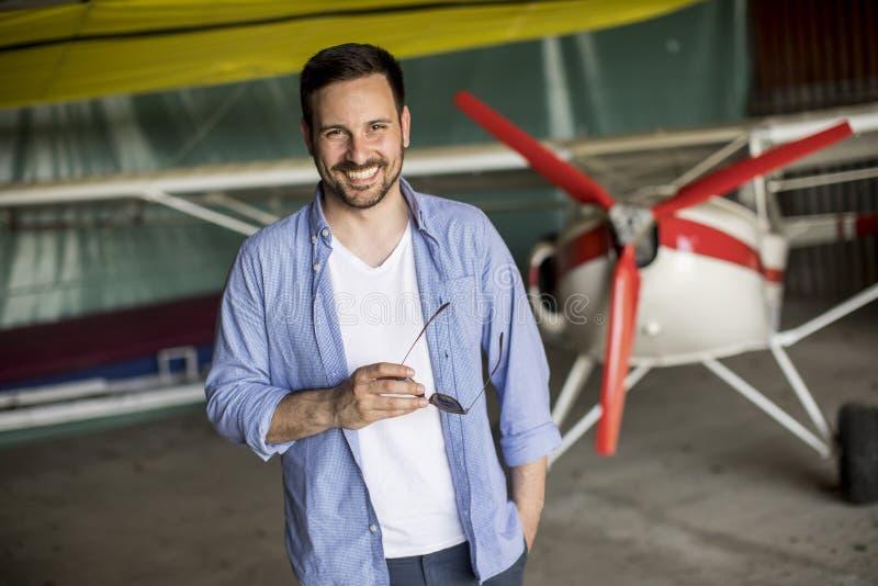Hombre joven en el hangar del aeroplano imágenes de archivo libres de regalías