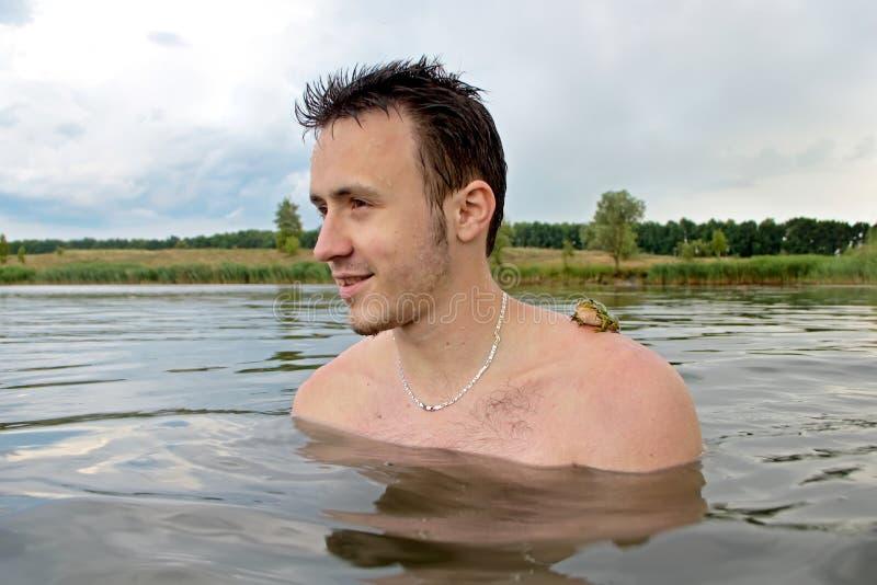 Hombre joven en el río con una rana en su hombro fotos de archivo libres de regalías