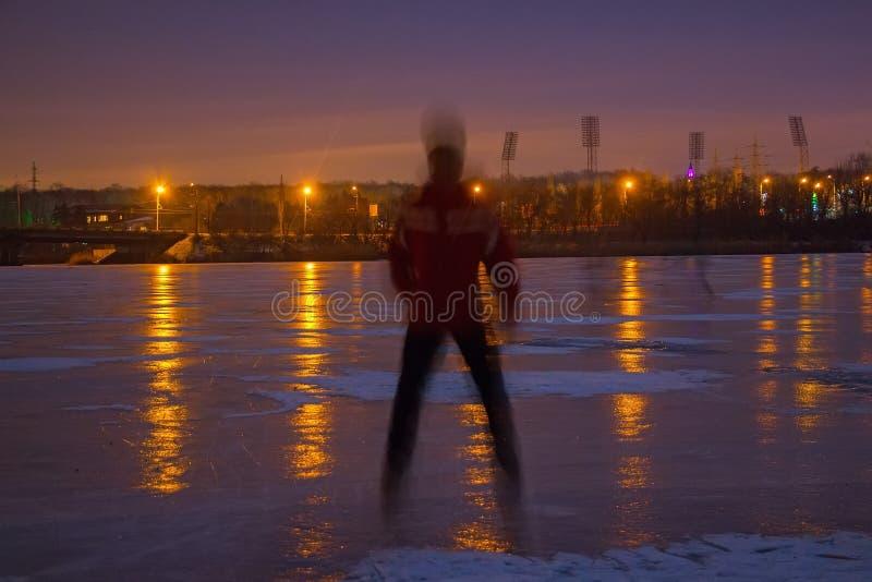 Hombre joven en el río congelado en la noche fotos de archivo libres de regalías
