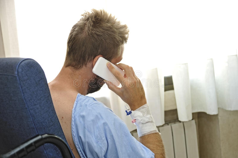 Hombre joven en el sitio de hospital que lleva los pijamas pacientes que se sientan por la ventana que habla en el teléfono móvil imagenes de archivo
