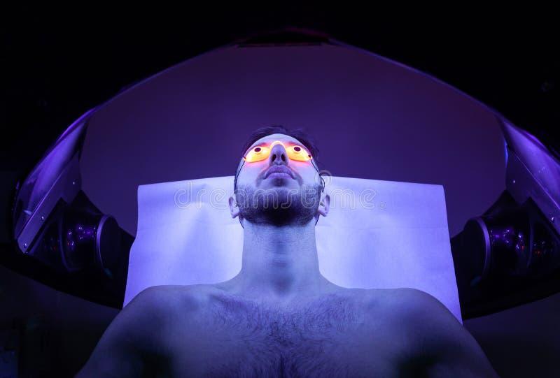 Hombre joven en el solarium en salón de belleza imagen de archivo libre de regalías