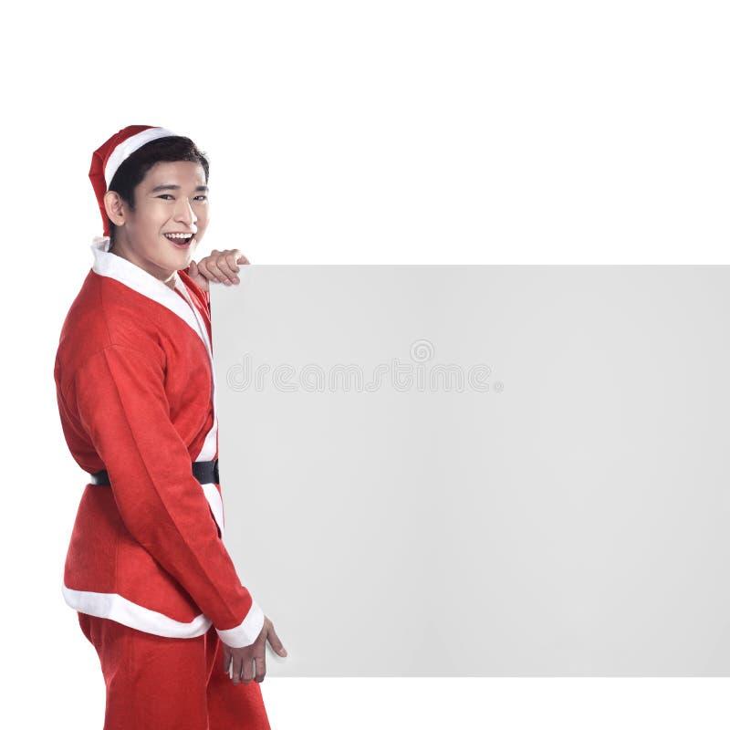 Hombre joven en el traje de Santa Claus detrás del tablero blanco imagen de archivo