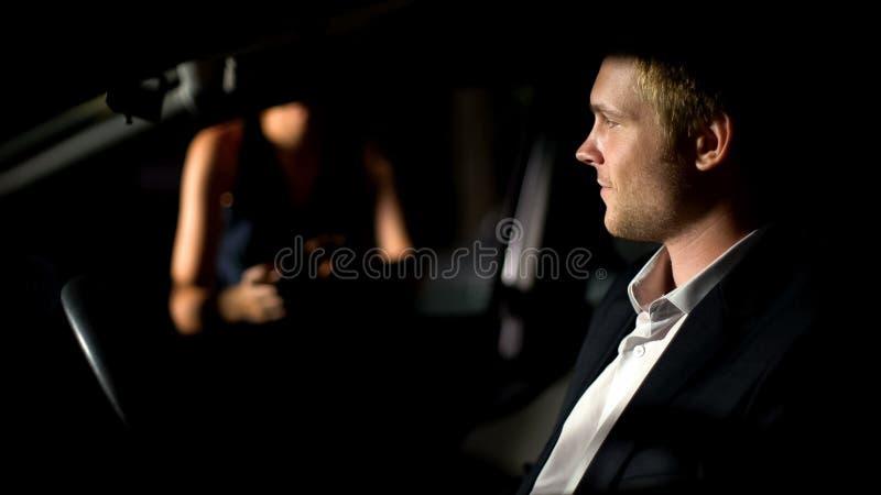 Hombre joven en el traje que se sienta en el coche y la mujer que espera, fecha romántica, tarde fotos de archivo libres de regalías
