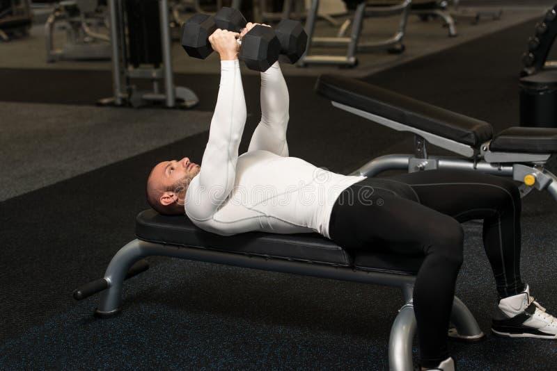 Hombre joven en gimnasio que ejercita el pecho con pesas de gimnasia imágenes de archivo libres de regalías