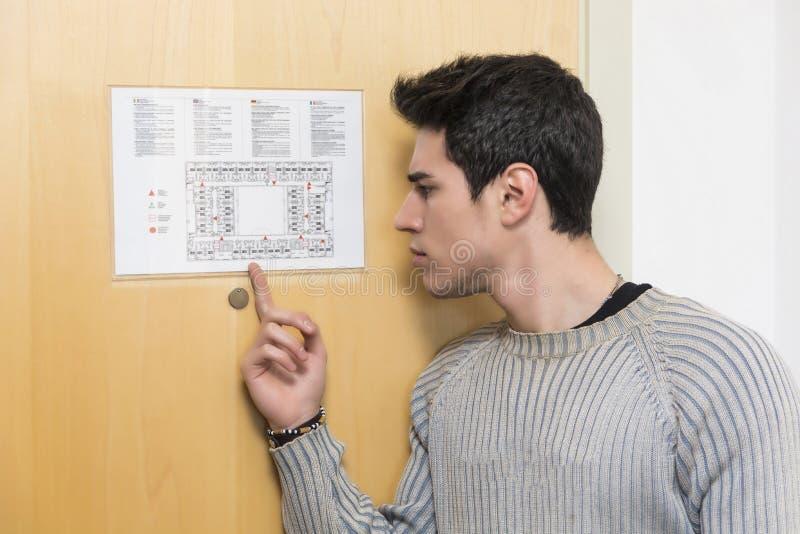 Hombre joven en hotel que señala en floorplan fotografía de archivo