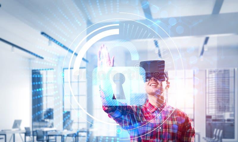 Hombre joven en interior moderno de la oficina que experimenta tecnología de la realidad virtual imagen de archivo libre de regalías