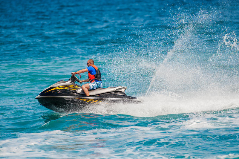Hombre joven en Jet Ski, océano tropical foto de archivo
