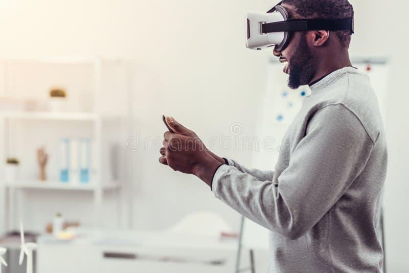Hombre joven en juegos casuales de la realidad virtual que juegan fotos de archivo