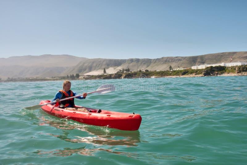 Hombre joven en kajak del mar imagen de archivo libre de regalías