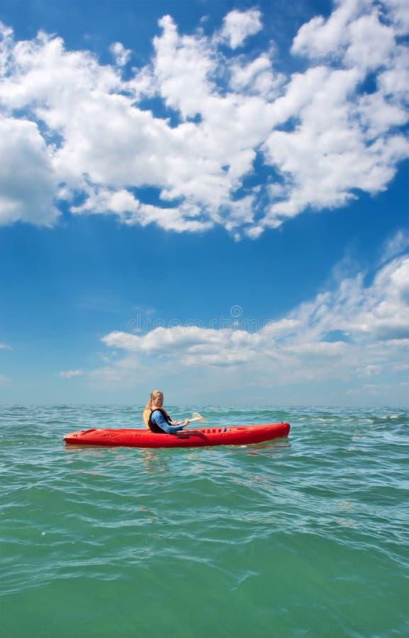 Hombre joven en kajak del mar bajo los cielos dramáticos imágenes de archivo libres de regalías