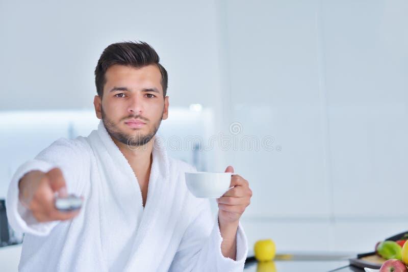 Hombre joven en la albornoz que se sienta en worktop de la cocina y que come una taza de té imagenes de archivo