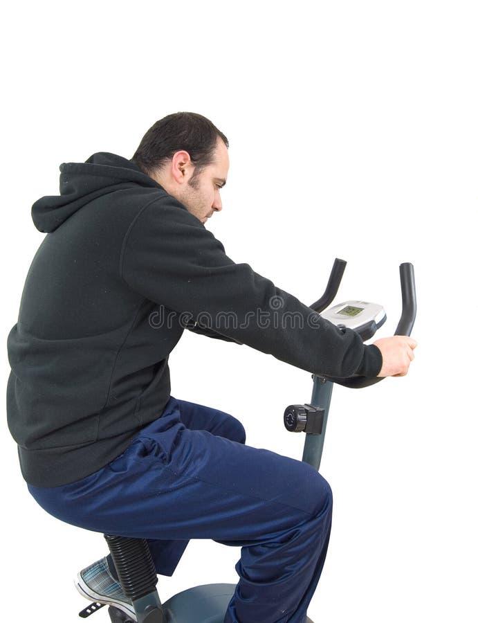 Hombre joven en la bicicleta inmóvil del entrenamiento imagen de archivo