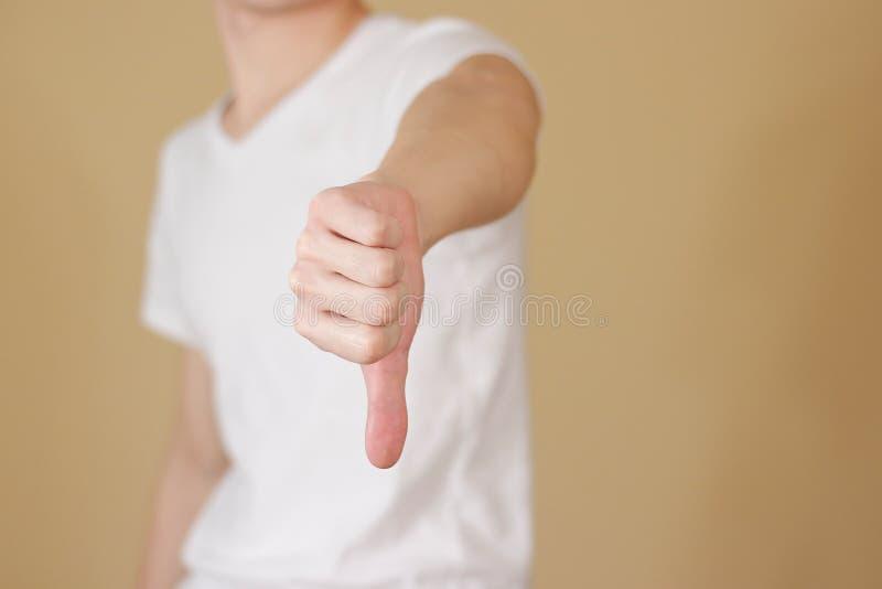 Hombre joven en la camiseta blanca que muestra una muestra de la aversión, o foto de archivo libre de regalías