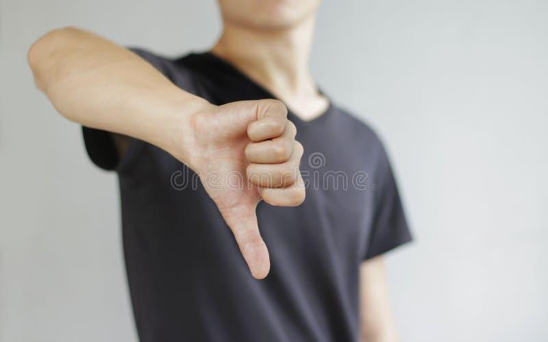 Hombre joven en la camiseta negra que muestra una muestra de la aversión, o aislado imagen de archivo libre de regalías