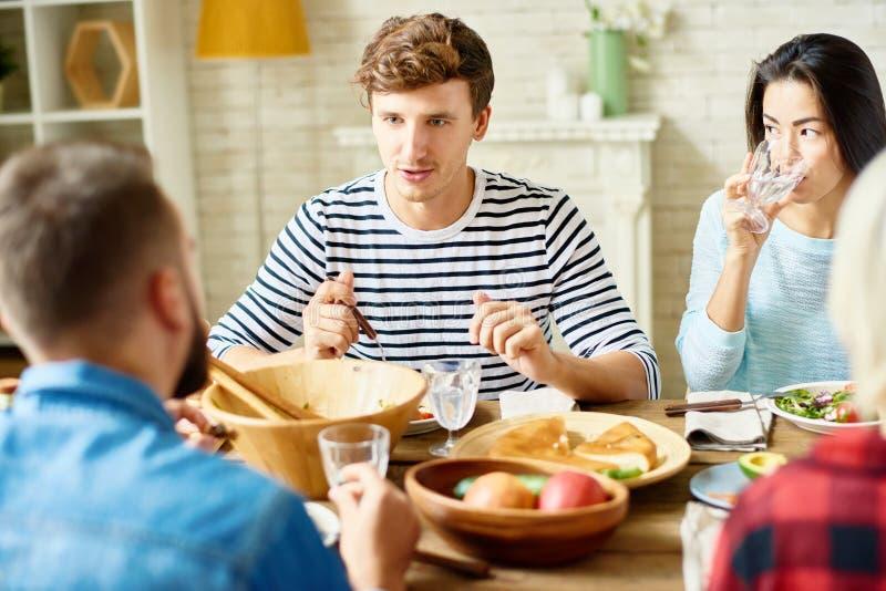 Hombre joven en la cena con los amigos imagenes de archivo