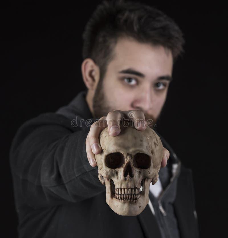 Hombre joven en la chaqueta negra que sostiene el cráneo imagenes de archivo