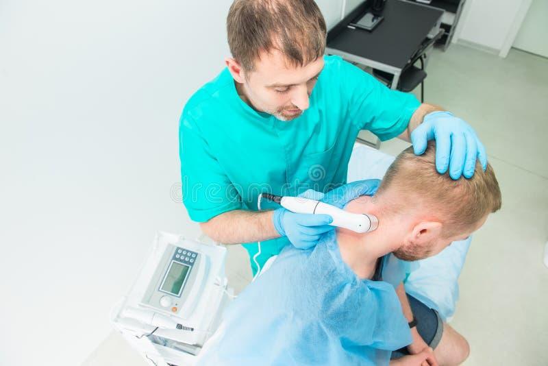 Hombre joven en la fisioterapia que recibe masaje de la terapia del laser Un quiropr?ctico trata la espina dorsal cervical del pa imagen de archivo libre de regalías