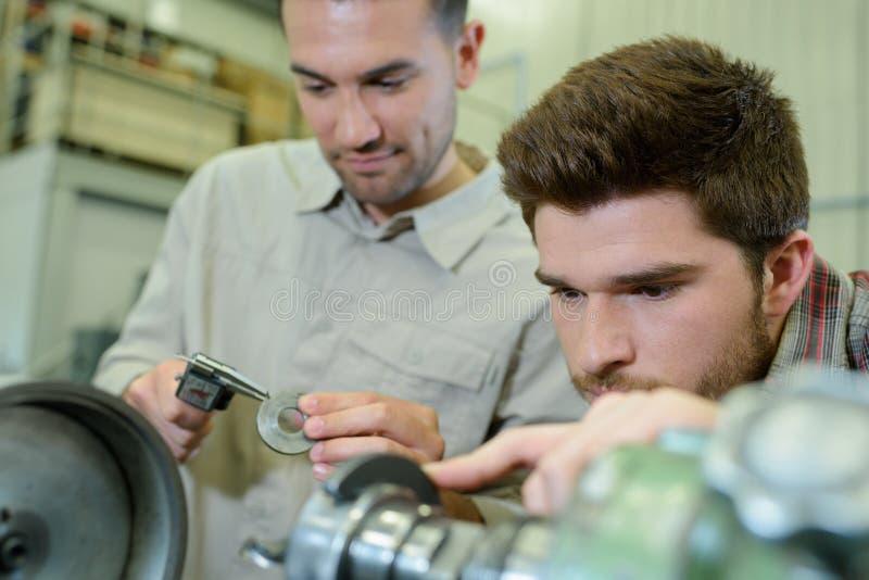 Hombre joven en la formación profesional técnica con el profesor imagenes de archivo