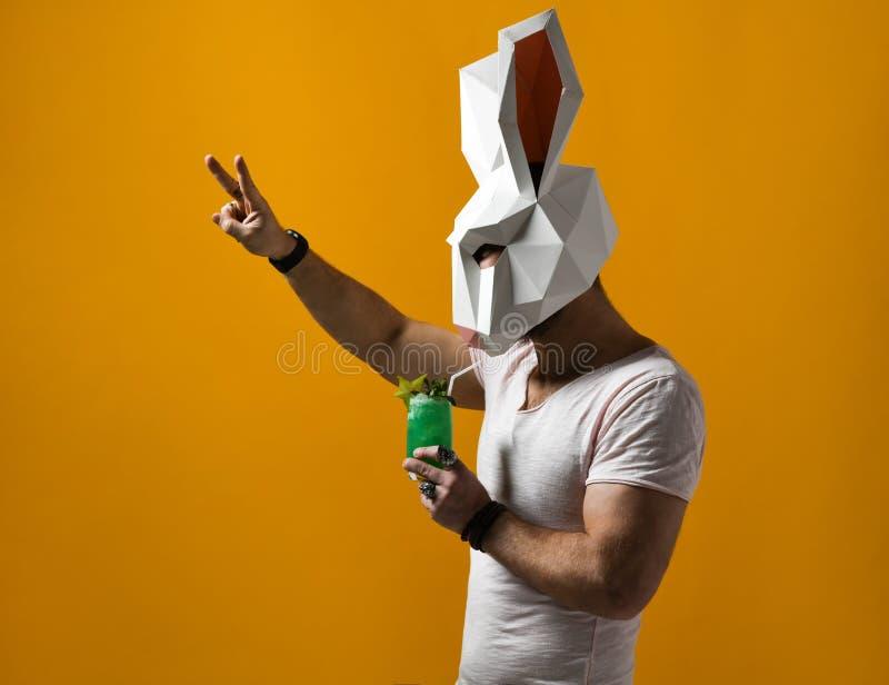 Hombre joven en la m?scara de papel del conejo y la camiseta blanca que bebe la bebida verde del c?ctel fotografía de archivo