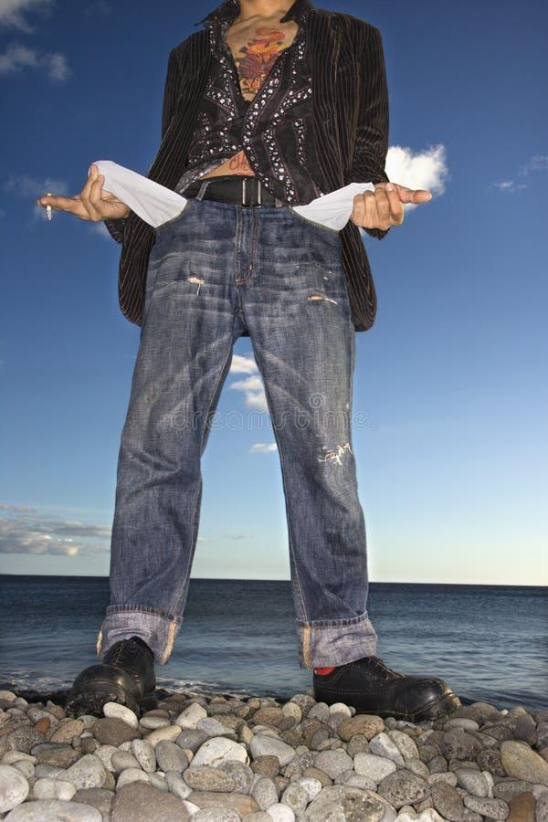 Hombre joven en la playa con los bolsillos vacíos imagen de archivo libre de regalías