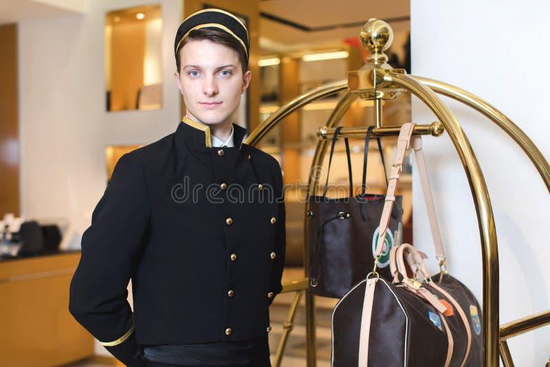 Hombre joven en la porción uniforme en hotel fotos de archivo
